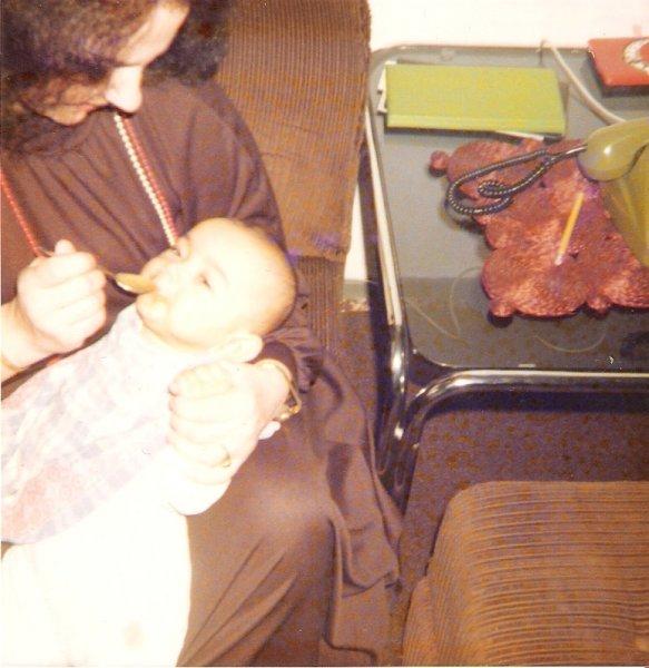 Mama füttert mich im Arm mit einen Löffel Brei